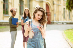 On foreground student girl in denim with phone and notebooks in her hands. Stock Image