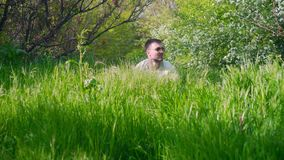In the foreground there is green juicy grass, in the background a man with glasses looks out of the grass. The head of a man with glasses peeps out of the stock video footage