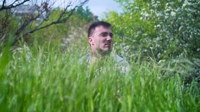 In the foreground there is green juicy grass, in the background a man looks out of the grass. The head of a man looks out of the grass stock footage