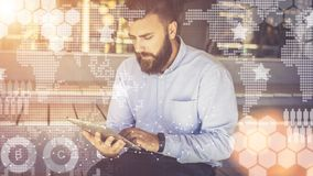 In foreground are virtual graphs,diagrams, charts. Hipster man blogging, chatting, learning online. Online marketing. Young bearded businessman is sitting and royalty free stock photo