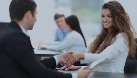 Beautiful female Manager shaking hands with a client at the work. In the foreground is a young women assistant with a handshake greets the client.photo on the Stock Photo