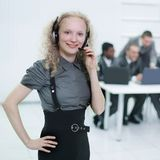 Foreground a young woman employee of a call center Stock Images