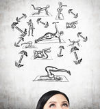 A forehead of a brunette woman who is thinking about crossfit trainings. Cross fit icons are drawn on the concrete wall Royalty Free Stock Photography