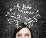 A forehead of the lady and maths formulas are drawn on the black chalkboard. A forehead of the brunette lady and maths formulas are drawn on the black Royalty Free Stock Photo
