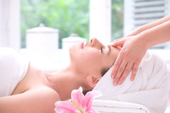 Forehead massage. Attractive young woman being pampered with a forehead massage stock images