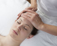 Forehead massage to remove migraine. Headache and stress relief at the spa Stock Image