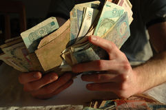 Foreign cash. Two hands hold a bundle of foreign currency like a deck of cards Stock Images