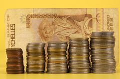 Foreign coins and notes on a yellow background Royalty Free Stock Images