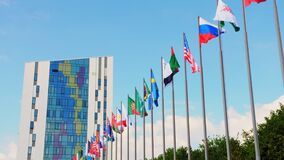 Foreign country flags waved by wind on poles under blue sky