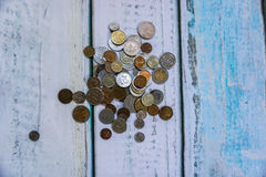 Foreign currency coins. On wooden floor Stock Photo