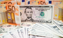 Foreign exchange. US banknotes on a fan of high-denomination european euro notes Stock Image