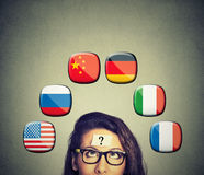 Foreign language studying process. Woman with question mark icons of international flags above head Stock Photography