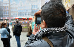 Foreign tourist takes pictures on Grand Place. BRUSSELS, BELGIUM-OCTOBER 23, 2014: Foreign tourist takes pictures on Grand Place royalty free stock photos
