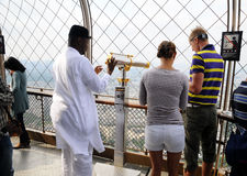 Foreign tourists with telescope on Eiffel tower Royalty Free Stock Image