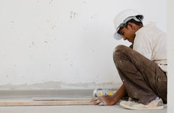 Foreign worker cutting wood in construction site Royalty Free Stock Photo