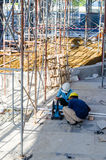 Foreign workers cutting construction material Stock Images