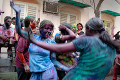 Foreigners in India. March 22, 2011. Free school street,Kolkata,West Bengal,India,Asia-A foreign woman dancing with the local people during the holi festival of Royalty Free Stock Photos