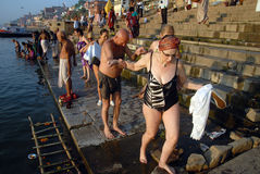 Foreigners in India. March 29,2013 Varanasi,Benaras,Uttar Pradesh,India,Asia-At early morning foreigners completed their holy bath and going carefully on the Royalty Free Stock Photography