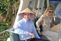 Foreignner z Wietnamskim tradycyjnym kapeluszem visitting Mekong deltę Vietnam na czółnie Zdjęcia Stock