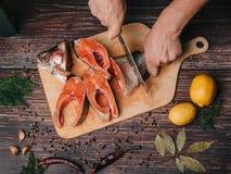 Forel op de Raad, die een mensenkok met een mes snijdt Verse ruwe rode vissen stock fotografie