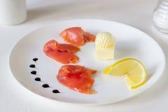 Forell, sm?r och citron p? en platta Vit bakgrund royaltyfri foto