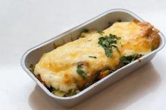 Forellen bakade med grönsaker och ost i grupperingsmagasin Royaltyfri Foto