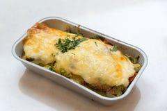 Forellen bakade med grönsaker och ost i grupperingsmagasin Royaltyfri Bild