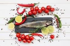 Forellfisken kritiserar på skärbrädan med körsbärsröda tomater, citronen, chilipeppar Royaltyfria Foton