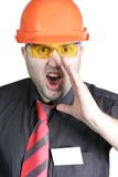 Foreman. The builder in a building helmet shouts on the isolated white background Stock Photo