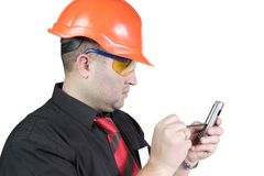 Foreman. The young builder in a building helmet with a mobile phone on the isolated white background Stock Image