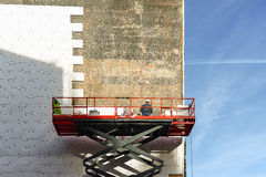 Foreman applying tile on wall building. On high scaffold  in good weather day in winter Stock Photo