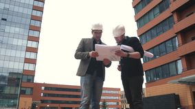 Foreman and architect at construction site. two men in construction helmets on the building location to discuss the plan. Architect young woman walking by a stock footage