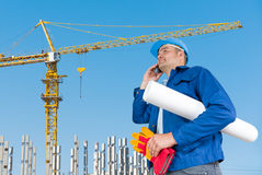 Foreman with blueprints. At construction site stock images