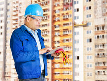 Foreman with blueprints. At construction site royalty free stock photography