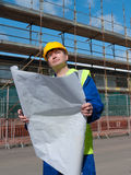 Foreman on buiding site looks up. Builder inspects plans and buildings on construction site Royalty Free Stock Photos
