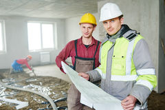 Foreman builder and construction worker with blueprint in indoor apartment Royalty Free Stock Photography