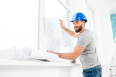 Foreman or builder with drawings. Portrait of a handsome builder, foreman or repairman in the helmet looking at the paper drawings near the window indoors Stock Images