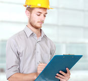 Foreman on building site with hard hat. Happy young foreman on building site with hard hat Royalty Free Stock Images