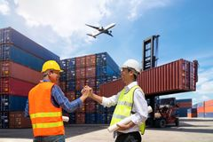 Foreman and Businessman control loading Containers. Box from Cargo freight ship Royalty Free Stock Image