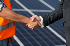 Foreman and businessman shaking hands at solar energy station. Close up view on handshake between worker and men in business suit stock photos