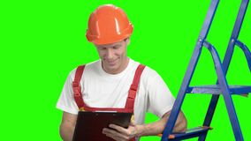 Foreman checking new object, green screen. Smiling project manager drawing plan on clipboard, chroma key background stock video footage