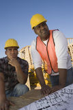 Foreman With Co-Worker Looking At Framework. At construction site royalty free stock photography