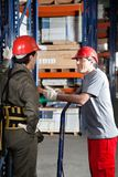 Foreman Communicating With Coworker At Warehouse Royalty Free Stock Photos