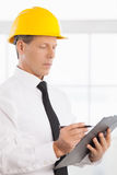 Foreman. Confident mature man in formalwear and hardhat writing something in his note pad Royalty Free Stock Image