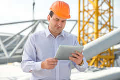A foreman at the construction. A foreman with digital tablet at the construction supervising the project stock image