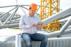 A foreman at the construction. A foreman with digital tablet at the construction supervising the project Stock Photos