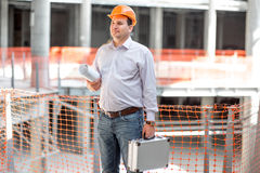 A foreman at the construction. A foreman with drawings and case supervising the project at the construction stock photography