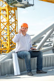 A foreman at the construction. A foreman with drawings speaking phone at the construction royalty free stock image