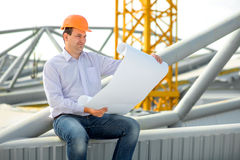 A foreman at the construction. A foreman with drawings supervising the project at the construction royalty free stock photography