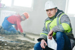 Foreman construction engineer worker portrait. Foreman builder and construction worker portrait in front of concrete floor covering in new indoor building flat Stock Photography